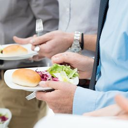 man holding a plate full of food at a corporate event