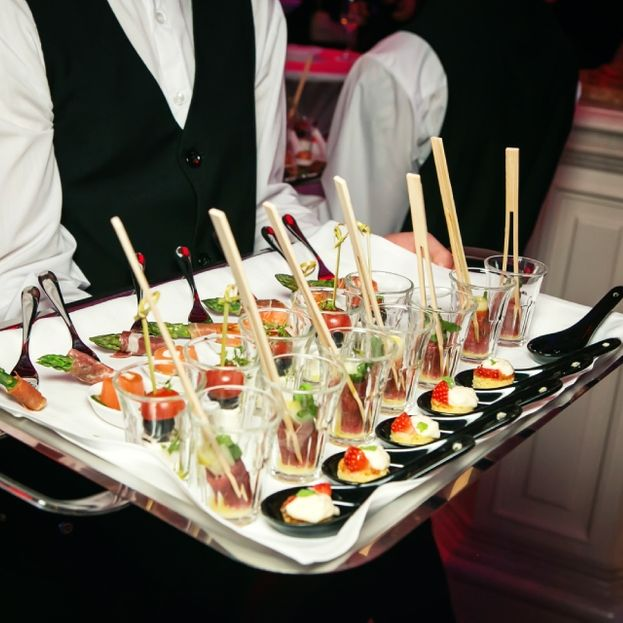 waiter holding a tray full of appetizers