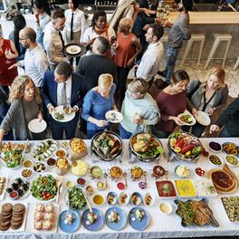 people looking at wide range of dishes served at an event