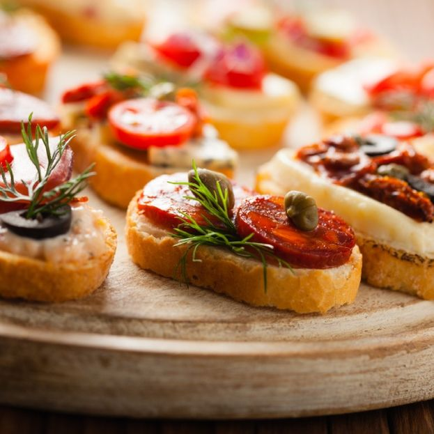 Crostini with different toppings on wooden surface